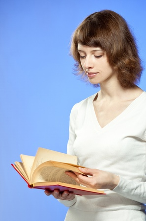 The girl turning over the pages of book;  coloured background Stock Photo - 12118991