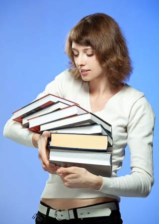 The young woman with stack of books;  coloured background Stock Photo - 12119066