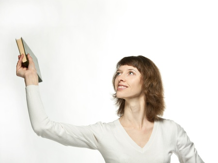 La niña saludando de la mano con un libro, fondo neutro Foto de archivo - 12118927
