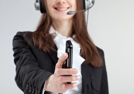 Call us! Call center operator woman reaching out mobile phone to client asking to call Stock Photo - 12119107