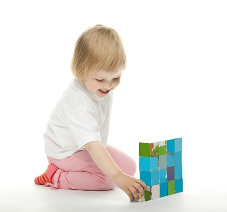 The happy baby girl playing with bricks; white background Stock Photo
