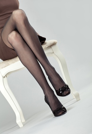 Legs of young lady in black stockings and high-heeled shoes; legs of young woman sitting on a chair photo
