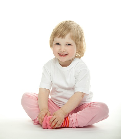 engaging: Smiling little girl sitting on the floor and engaging in yoga; white background