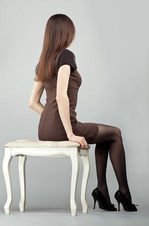 ülő: Elegáns, hosszú hajú, barna lány ruhában ül egy széken, hátsó kilátás; műterem lövés semleges háttér