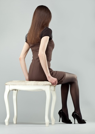 legs stockings: Elegant long-haired brunette girl in dress sitting on a chair, rear view; studio shot on neutral background Stock Photo