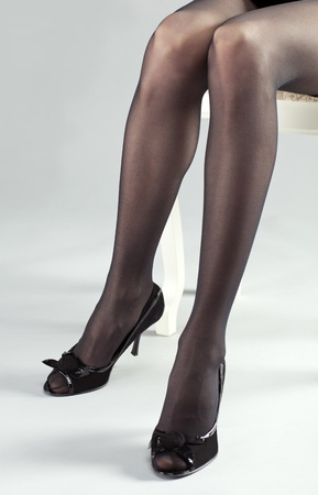 Long legs of young woman wearing black stockings and high-heeled shoes photo