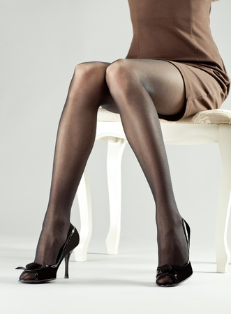 legs stockings: Legs of young woman wearing mini dress and high-heeled black shoes