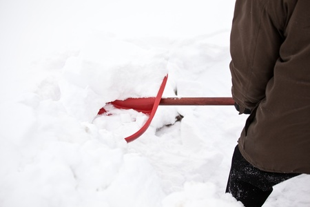 Man removing snow with a red shovel photo