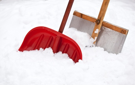 Two shovels for snow removal in fresh snow