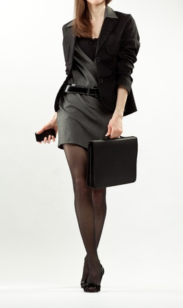 Elegant businesswoman walking with a cellphone and briefcase; full length portrait on neutral background photo