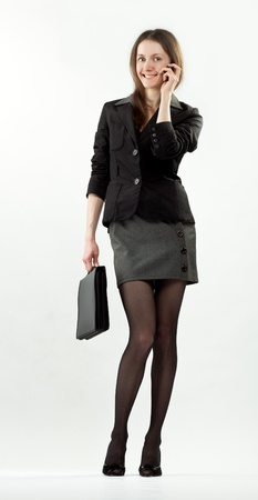 Happy smiling businesswoman speaking on the mobile phone holding briefcase; full length portrait on neutral background photo