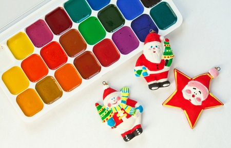 Colorful paints set and new year toys painted by a child; neutral background photo