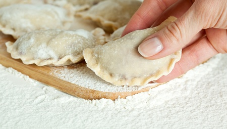 Dumplings in flour on the wooden board; hand holding varenik before cooking photo