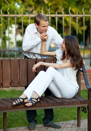Beautiful romantic young couple in love sitting on the bench in a park photo