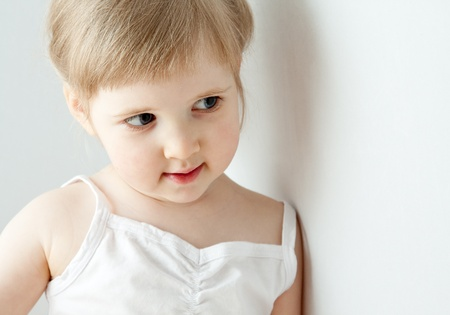 The beautiful little girl leaning on the wall; neutral background Stock Photo - 12301925