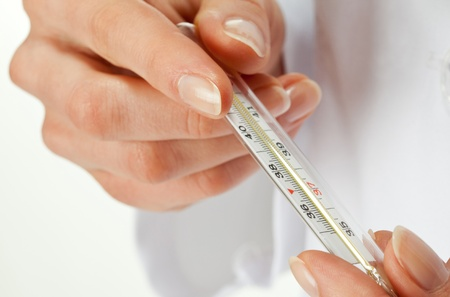 Taking temperature: closeup of hands holding thermometer Stock Photo
