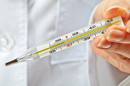 Closeup of doctors hands showing normal temperature on thermometer photo
