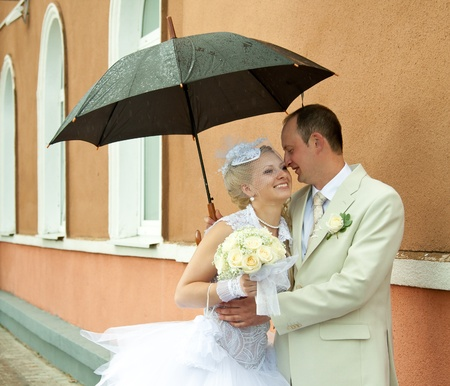 Happy bride and groom embracing under an umbrella photo