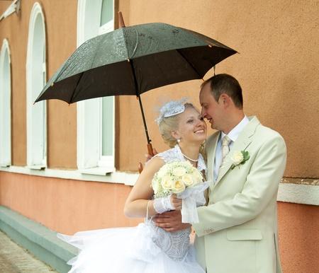 Happy bride and groom embracing under an umbrella Stock Photo - 12302007