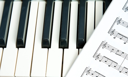 A music book lying on the keys of a piano photo