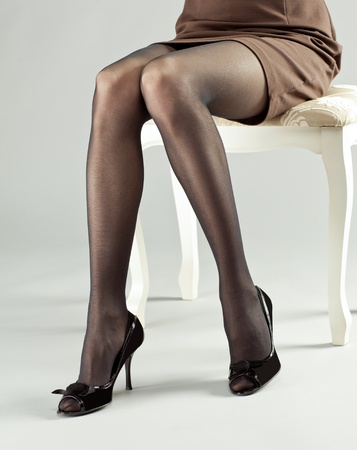 Legs of young woman wearing mini dress and high-heeled black shoes