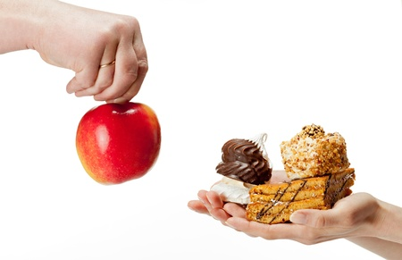 high calorie: Hands proposing apple (healthy food) and cakes (unhealthy food) to each other. Concept of making a choice: healthy low-calorie or unhealthy high-calorie food?  Isolated on white