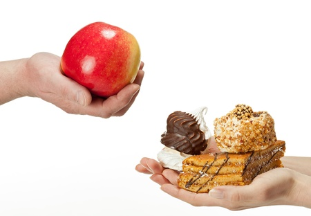 Hands proposing apple (healthy food) and cakes (unhealthy food) to each other. Concept of making a choice: healthy low-calorie or unhealthy high-calorie food?  Isolated on white