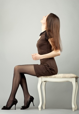 banquette: Elegant young brunette sitting on a banquette; neutral background Stock Photo