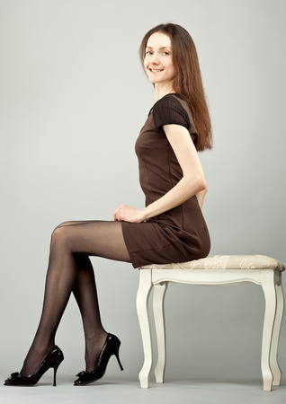 Elegant young smiling brunette sitting on a banquette; neutral background
