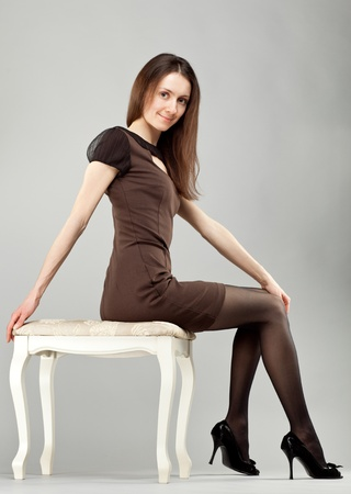 Young beautiful brunette girl in dress sitting on banquette; neutral background photo