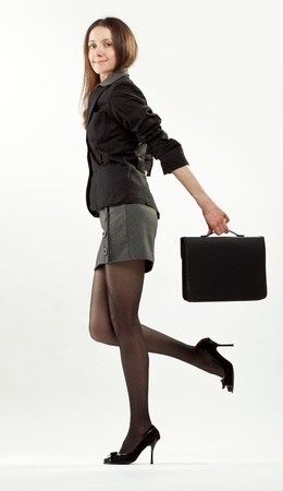 high heel shoes: Young brunette (businesswoman or student) holding briefcase wearing dress and high heel shoes; full length studio portrait on neutral background Stock Photo