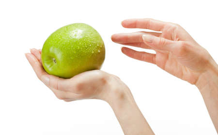 dietology: Human hands holding fresh green apple with drops of water; isolated over white background