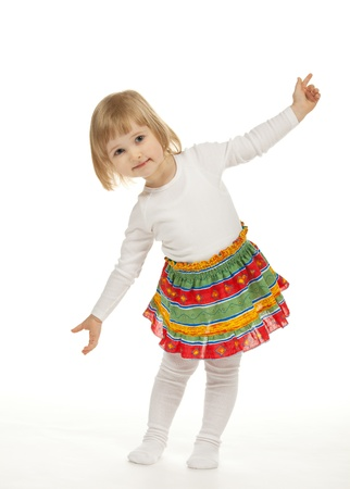 The smiling little girl dancing on white background photo