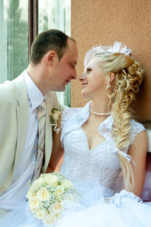 The young beautiful couple embracing in wedding day photo