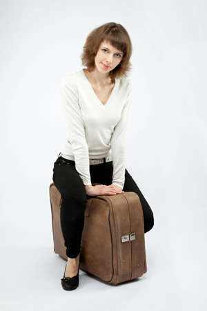 The smiling young woman sitting on a big trunk; neutral background Stock Photo - 12663734