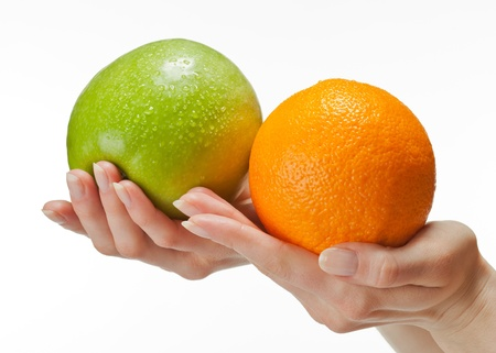 dietology: Human hands holding fresh appetizing fruits (orange and apple); isolated over white background Stock Photo