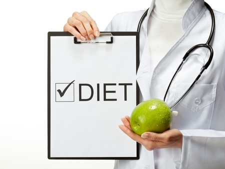 donne obese: Primo piano delle mani del medico in possesso appunti con checkbox marcata e mela verde isolato su sfondo bianco