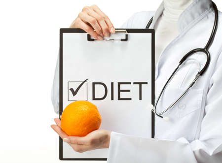 Doctor prescribing diet; closeup of doctors hands holding clipboard with marked checkbox Diet and orange; isolated on white background photo