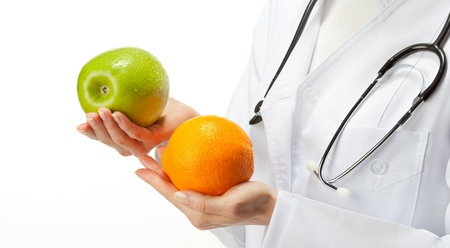 dietetics: Doctor prescribing healthy eating: closeup of doctors hands holding fruits; isolated on white background Stock Photo