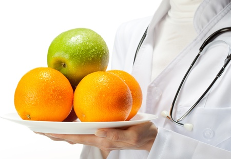 dietology: Doctor prescribing healthy eating: closeup of doctors hands holding plate with fresh fruits; isolated on white background