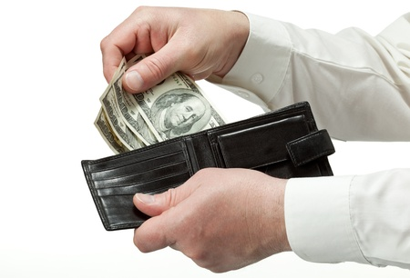 Closeup of man's hands holding leather wallet with dollars; isolated over white background photo