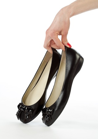 flat foot: Hand holding pair of flat shoes on white background