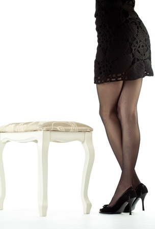 Beautiful legs of young woman staying near banquette on white background photo