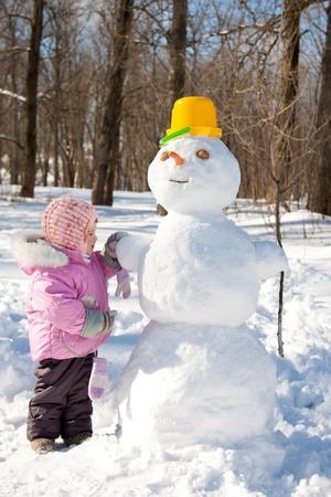 A little girl touching a snowman Stock Photo