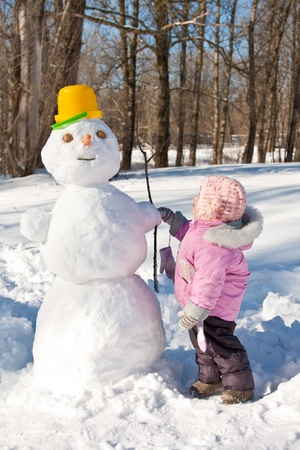 A little girl touching a snowman photo