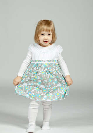 The smiling little girl staying and holding her beautiful dress; neutral background photo
