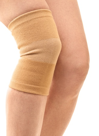 Closeup of a woman legs with one compression knee brace; isolated on white photo