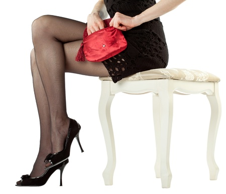 Beautiful legs of young woman sitting on banquette holding red handbag; isolated over white background photo