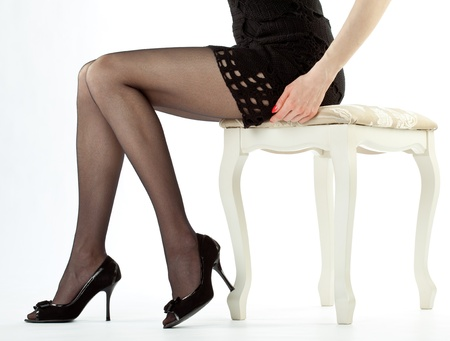 Beautiful legs of young woman sitting on banquette; isolated over white background photo