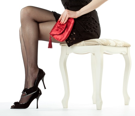 Beautiful legs of young woman sitting on banquette holding red handbag; isolated over white background